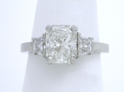 Three stone diamond ring with 1.51 carat cut-cornered rectangular modified brilliant (radiant) cut diamond set in a custom platinum basket-style mounting with matched pair of brilliant trapezoid cut diamonds