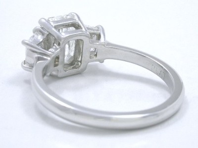 Radiant cut diamond ring with radiant prong set in a custom platinum three-stone mounting with a pair of matching brilliant cut trapezoid side diamonds