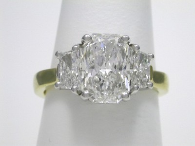 Radiant cut diamond engagement ring with custom 18-karat yellow gold and platinum three stone mounting with a pair of brilliant trapezoid cut diamonds