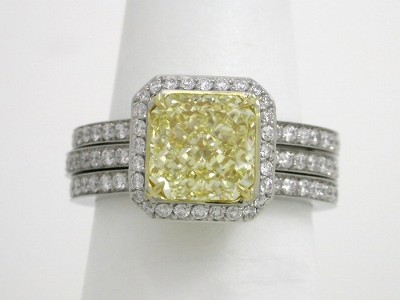 Fancy Intense Yellow radiant cut diamond ring with platinum, parallel split-shank style mounting with an 18-karat yellow-gold bezel surrounding the center stone