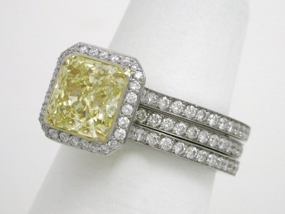 Fancy Intense Yellow radiant cut diamond ring with platinum, parallel split-shank style mounting with an 18-karat yellow-gold bezel surrounding the center stone and matchind diamond interlocking band