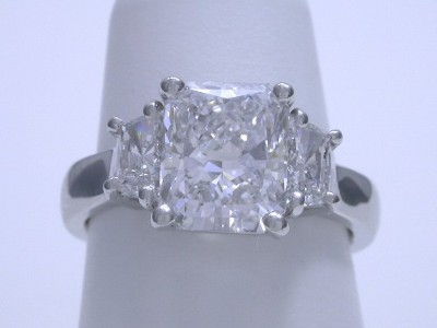 Radiant cut diamond engagement ring with custom platinum three stone mounting with a pair of matched trapezoid brilliant diamonds in basket style heads