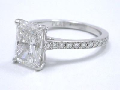 Radiant cut diamond ring has modified basket so that the ring will accommodate a flush fitting wedding band