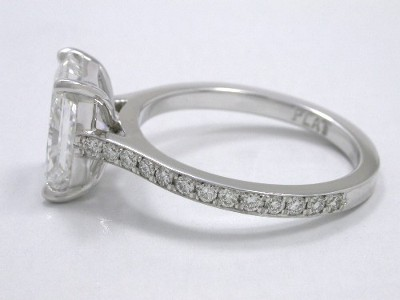 Radiant cut diamond ring with custom platinum mounting with modified basket head and pave-set round diamonds going three quarters the way down the top of the shank