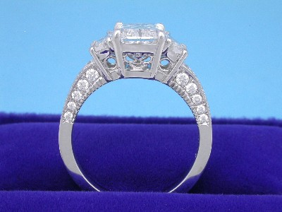 "Radiant and trapezoid cut diamond ring with custom platinum (stamped ""PLAT"") three-stone mounting with filigree scroll design on the sides of the baskets and milgrain edging and pave-set round brilliant-cut diamonds on the top and sides of shoulders of the shank"