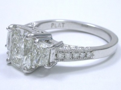 Radiant cut diamond ring with custom platinum three stone mounting with a pair of matched trapezoid diamonds, pave-set round diamonds going half way down the three sides of the shank, and milgrain edging.