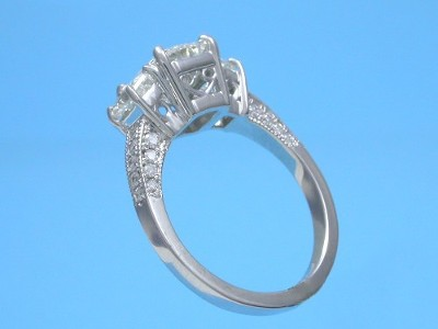 Radiant and trapezoid three-stone diamond engagement ring with pave shank