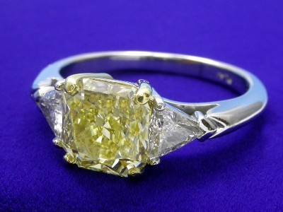 Fancy yellow square radiant diamond is held in an 18-karat yellow gold basket style head with a pair of matched trillion side stone diamonds set in platinum three-prong basket style heads