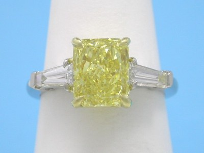 Diamond ring with Fancy Intense Yellow cut-cornered rectangular modified brilliant (radiant) cut diamond with step-cut tapered baguette side diamonds