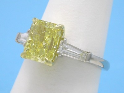 Fancy Intense Yellow color radiant cut diamond ring with a pair of step-cut tapered baguettes having set in a custom platinum and 18-karat yellow-gold three-stone mounting