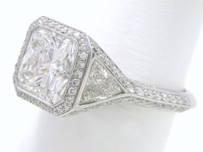 Square radiant cut diamond ring with side trillion diamonds outlined by pave-set round diamonds in a Bez Ambar designer mounting