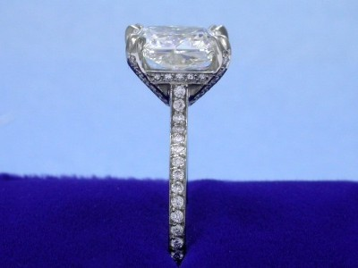 Radiant cut diamond ring with custom platinum Bez Ambar mounting with split-prong Paloma head and pave-set round diamonds going half way around the band and going up the prongs