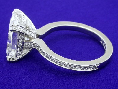 Radiant cut diamond prong-set in a split-prong custom Bez Ambar designer platinum pave mounting with pave set diamonds going three quarters the way around the shank and covering the basket and the prongs