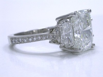 Radiant cut diamond ring with custom platinum three-stone mounting with a pair of brilliant trapezoid diamonds set in basket style heads and with pave-set diamonds of graduated size going half way down each side of the shank