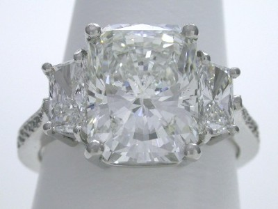 Diamond ring with 4.00 carat cut-cornered rectangular modified brilliant (radiant) cut diamond and side brilliant trapezoid cut diamonds in a three-stone mounting with pave