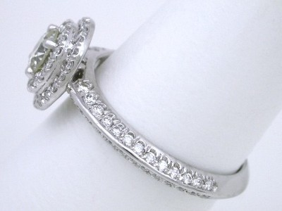 0.47-carat round brilliant cut diamond prong set in tiered mounting with round diamonds French cut pave-set on top of the double-halo and going three-fourths the way down the double-row knife edge shank