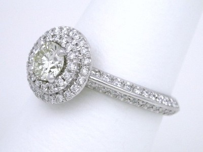 Custom platinum tiered mounting with round brilliant cut diamonds French cut pave-set on top of the double-halo and in graduated sizes going three-fourths the way down the double-row knife edge shank