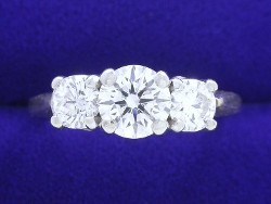 0.74 carat Round Brilliant Cut diamond in 3 Stone mounting with 0.60 total carat weight side Round Diamonds