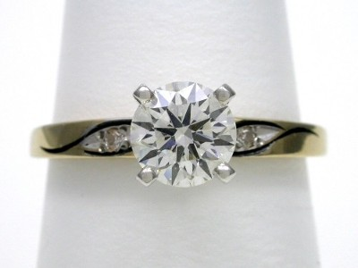 Round brilliant cut diamond engagement ring with swirl design mounting