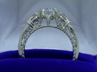 Round diamond ring has exquisite design with rivets milgrain and hatching border on the sides of the engagement ring