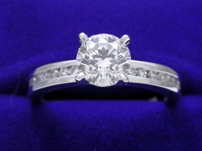 Diamond engagement ring with round brilliant diamond set in a custom 14-karat white-gold mounting with twenty channel-set round brilliant cut diamonds