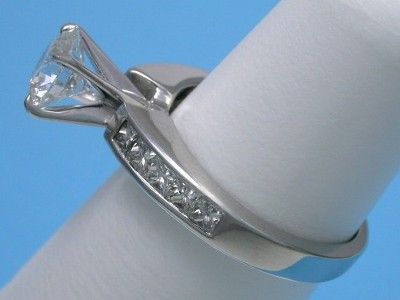 Round brilliant cut diamond engagement ring with channel-set princess diamonds on the shank