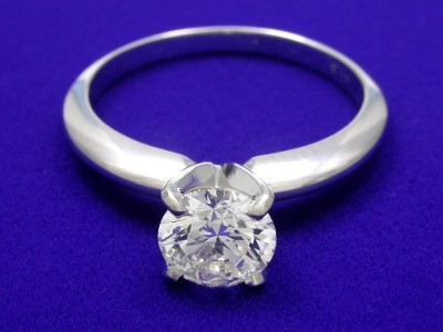 Round diamond ring with 14-karat white-gold with a four-prong head and knife-edge shank