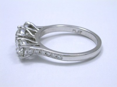 Round brilliant cut three-stone ring with round pave-set diamonds on the shank