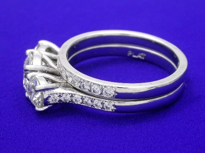 Round brilliant cut three-stone ring with round pave-set diamonds on the shank shown with matching diamond band
