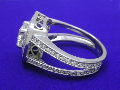 The mounting has two rows of bead-set diamonds around the center diamond and bead-set diamonds going down the top of the split-shank with milgrain edging
