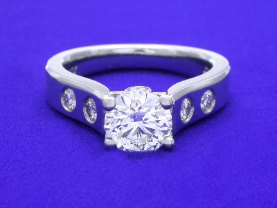 Trellis style mounting that has four round channel-set diamonds going half way down the shoulders of the shank and two round channel-set diamonds set on either side of the bridge