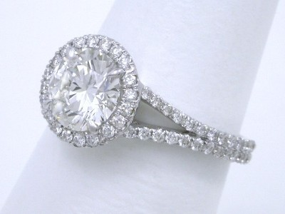 Round diamond ring with French cut pave-set round brilliant cut diamonds in the halo around the center stone and a little more than half the way down the top of the split shank