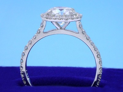 Round brilliant cut diamond ring with bead-set round diamonds in a halo around the center diamond and French pave-set round diamonds on top of the cathedral shank
