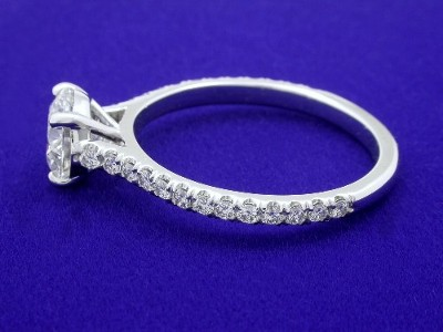 Round brilliant cut diamond prong-set in a platinum four-prong mounting with pave-set diamonds going three quarters of the way down the cathedral style shank