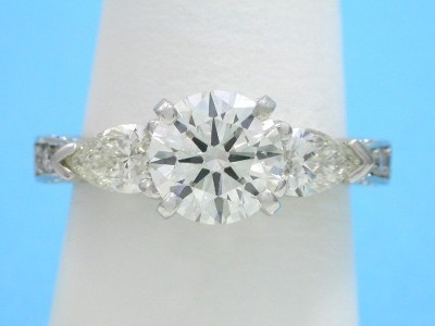 Round diamond ring with pear shaped side diamonds, graduated pave and hand engraving