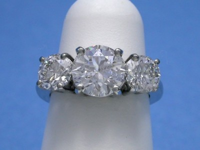 Round three stone diamond engagement ring with basket style mounting