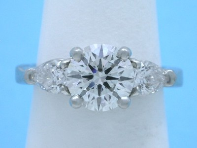 Round and pear cut diamond engagement ring with three-stone basket-style mounting