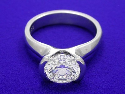 Round brilliant cut diamond engagement ring with platinum half bezel mounting