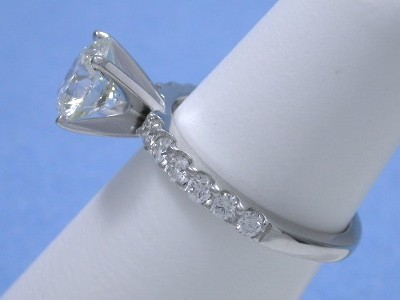 Round diamond prong set in a custom 14-karat white-gold mounting with a four prong solitaire style head and twelve shared-prong set round diamonds going half-way down the top of the shank