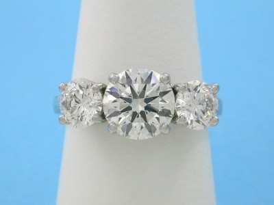 Round 1.50 carat diamond set in a custom platinum three-stone mounting with a pair of matched round brilliant diamonds with 1.02 total carat weight prong set in basket style heads