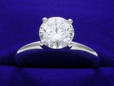 Round brilliant cut diamond prong set in a platinum solitaire mounting with four-prong head and knife-edge shank