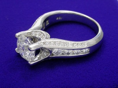 Round diamond ring has a center row of four round diamonds channel-set graduating in size on either side of the center stone going half way down the shank, two curved rows of pave-set round diamonds on the bridge under the center diamond and a single row on each side going half way down the shank