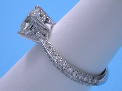 Round diamond ring with custom platinum mounting that has pave-set round diamonds in a knife-edge style going three-quarters of the way down the shank and four pave-set diamonds between the prongs on each side of the four-prong basket head