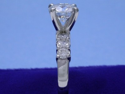 Round brilliant cut diamond ring in Leo Ingwer designer mounting with shared-prong set round diamonds