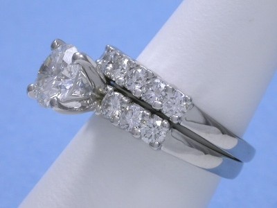 Round brilliant cut diamond ring in Leo Ingwer designer mounting with shared-prong set round diamonds with matching diamond band