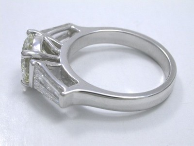Round brilliant cut diamond engagement ring with tapered baguette cut diamond side stones
