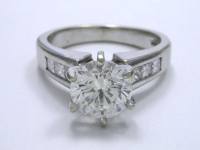 Round brilliant cut diamond engagement ring with 6-prong head and channel-set princess diamonds on the shank