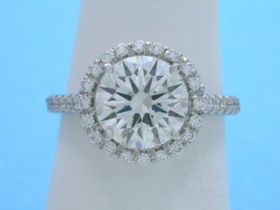 Round brilliant cut diamond engagement ring with pave halo and on the shank