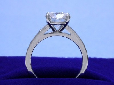 Round brilliant cut diamond engagement ring with bead-set diamonds going half way down the shank