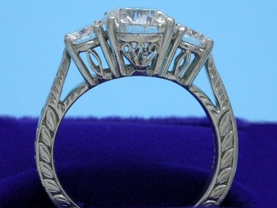 Round brilliant cut diamond three-stone engagement ring with platinum mounting decorated with an engraved foliate design and the galleries beneath the main diamonds decorated with open scroll work